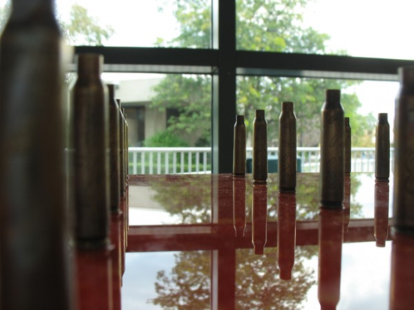 """60 shots, 1 victim (Anbar)"" 60 engraved and patined .223 shell casings on inked plexi, 2006, 45 x 20 x 3.25″"