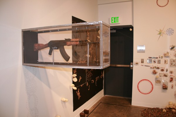 """Field Notes: Revisions Installation Exhibition View""  Hand Engraved AK47 with Mixed Media, Site Specific, 2010"