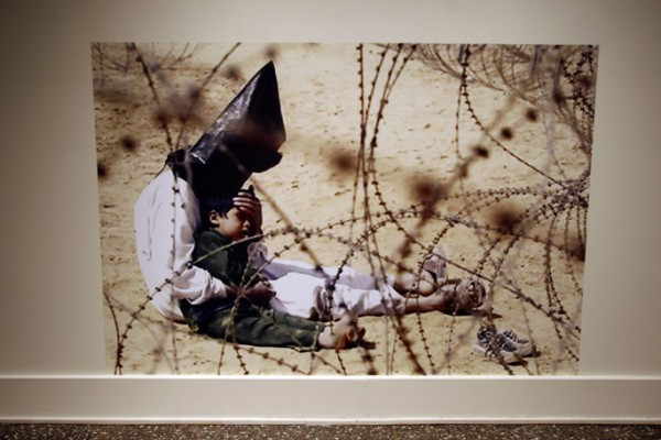 """""""Iraqi Detainee With Son in Winter Couture"""" appropriated image printed life size and presented at ground level, pigment print on adhesive vinyl, 2007, 42 x 75″"""