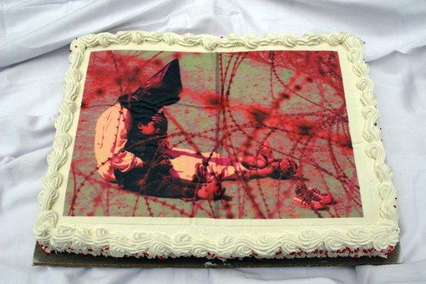 """""""Let Us Eat Cake No. 2 (Iraqi Detainee w/Son)"""" edible pigment print on decorated cake with sprinkles, presented in reception area of exhibition, 2007, 19 x 13 x 3″"""